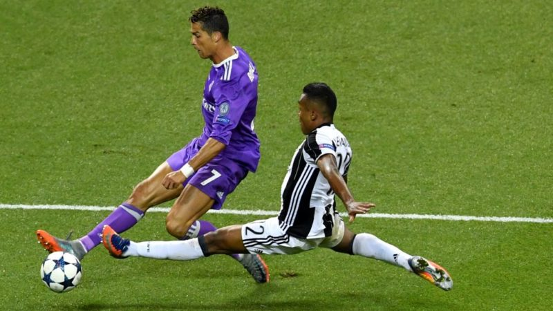 Juventus' Brazilian defender Alex Sandro (R) tackles Real Madrid's Portuguese striker Cristiano Ronaldo (L) during the UEFA Champions League final football match between Juventus and Real Madrid at The Principality Stadium in Cardiff, south Wales, on June 3, 2017. / AFP PHOTO / Ben STANSALL