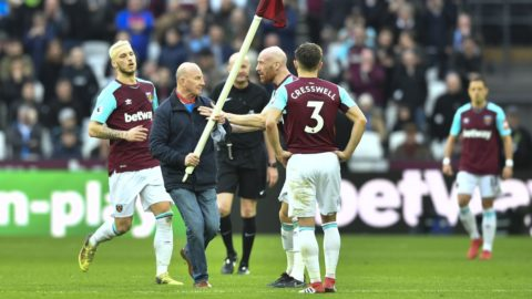 West Ham United's Welsh defender James Collins  (2R) confronts a pitch invader carrying a corner flag during the English Premier League football match between West Ham United and Burnley at The London Stadium, in east London on March 10, 2018. / AFP PHOTO / Ben STANSALL / RESTRICTED TO EDITORIAL USE. No use with unauthorized audio, video, data, fixture lists, club/league logos or 'live' services. Online in-match use limited to 75 images, no video emulation. No use in betting, games or single club/league/player publications.  /