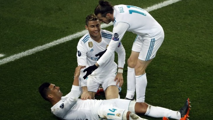 Real Madrid's Brazilian midfielder Casemiro (L) celebrates with Real Madrid's Portuguese forward Cristiano Ronaldo (C) and Real Madrid's Welsh forward Gareth Bale (R) after scoring his team's second goal  during the UEFA Champions League round of 16 second leg football match between Paris Saint-Germain (PSG) and Real Madrid on March 6, 2018, at the Parc des Princes stadium in Paris. / AFP PHOTO / Thomas SAMSON