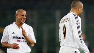 Real Madrid's Brazilian defender Roberto Carlos (L) jokes with his teammate compatriot Ronaldo against AS Roma, during their Champions League group B football match, 08 December 2004 at the Olympic stadium in Rome. Spectators are banned from the Olympic stadium due to UEFA sanctions imposed upon the troubled Italian side after referee Anders Frisk was hit by a missile thrown from the crowd at their home match against Dynamo Kiev in September. Madrid won 3-0. AFP PHOTO/ Patrick HERTZOG / AFP PHOTO / PATRICK HERTZOG