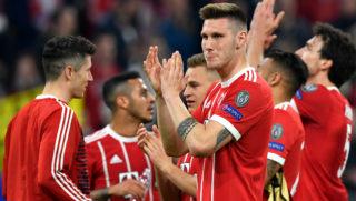 Bayern Munich's players react after the UEFA Champions League quarter-final second leg football match between FC Bayern Munich and Sevilla FC on April 11, 2018 in Munich, southern Germany. / AFP PHOTO / John MACDOUGALL