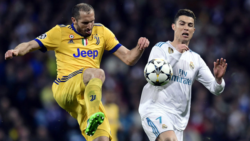 Juventus' Italian defender Giorgio Chiellini (L) vies with Real Madrid's Portuguese forward Cristiano Ronaldo (R) during the UEFA Champions League quarter-final second leg football match between Real Madrid CF and Juventus FC at the Santiago Bernabeu stadium in Madrid on April 11, 2018. / AFP PHOTO / JAVIER SORIANO