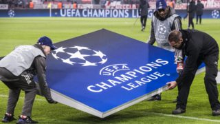 Workers carry a giant Champions League logo prior to the start of the UEFA Champions League round of sixteen first leg football match Bayern Munich vs Besiktas Istanbul on February 20, 2018 in Munich, southern Germany. / AFP PHOTO / John MACDOUGALL