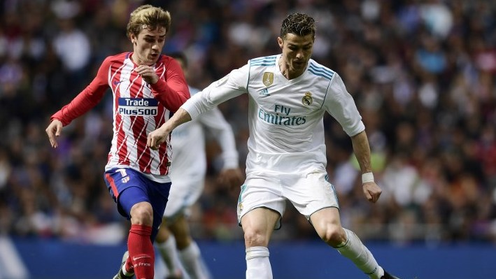 Real Madrid's Portuguese forward Cristiano Ronaldo (R) vies with Atletico Madrid's French forward Antoine Griezmann during the Spanish league football match between Real Madrid CF and Club Atletico de Madrid at the Santiago Bernabeu stadium in Madrid on April 8, 2018. / AFP PHOTO / JAVIER SORIANO