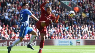 Liverpool's Dutch defender Virgil van Dijk (R) kicks the ball away by Brighton's English defender Lewis Dunk during the English Premier League football match between Liverpool and Brighton and Hove Albion at Anfield in Liverpool, north west England on May 13, 2018. / AFP PHOTO / Paul ELLIS / RESTRICTED TO EDITORIAL USE. No use with unauthorized audio, video, data, fixture lists, club/league logos or 'live' services. Online in-match use limited to 75 images, no video emulation. No use in betting, games or single club/league/player publications.  /