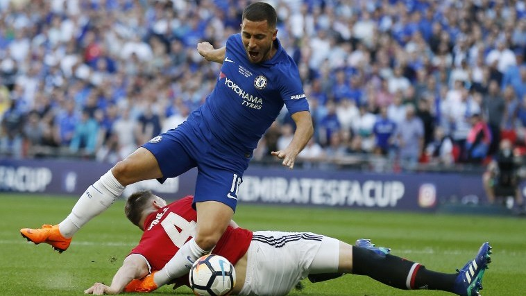 Manchester United's English defender Phil Jones (down) fouls Chelsea's Belgian midfielder Eden Hazard to give away a penalty during the English FA Cup final football match between Chelsea and Manchester United at Wembley stadium in London on May 19, 2018. / AFP PHOTO / Ian KINGTON / NOT FOR MARKETING OR ADVERTISING USE / RESTRICTED TO EDITORIAL USE