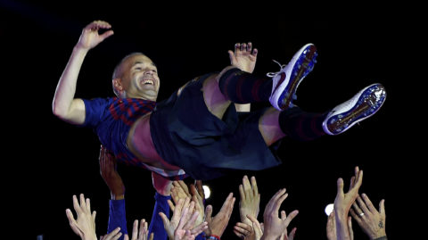 Barcelona's Spanish midfielder Andres Iniesta is thrown in the air by teammates during a tribute at the end of the Spanish league football match between FC Barcelona and Real Sociedad at the Camp Nou stadium in Barcelona on May 20, 2018. Iniesta, who joined Barcelona's academy 22 years ago, played his final game for the club. / AFP PHOTO / LLUIS GENE