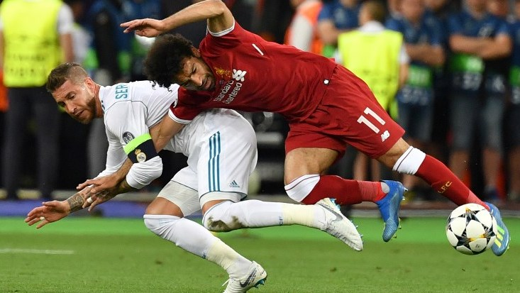 Liverpool's Egyptian forward Mohamed Salah (R) falls with Real Madrid's Spanish defender Sergio Ramos leading to Salah being injured during the UEFA Champions League final football match between Liverpool and Real Madrid at the Olympic Stadium in Kiev, Ukraine, on May 26, 2018. / AFP PHOTO / GENYA SAVILOV