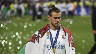 Real Madrid's Welsh forward Gareth Bale with his winner's medal and a Welsh flag on the pitch as Real Madrid players celebrate winning the UEFA Champions League final football match between Liverpool and Real Madrid at the Olympic Stadium in Kiev, Ukraine on May 26, 2018. Real Madrid defeated Liverpool 3-1. / AFP PHOTO / Paul ELLIS