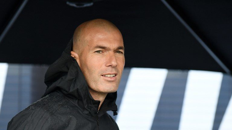 Former French football player and former Real Madrid coach Zinedine Zidane looks on as he shelters under an umbrella in Saint Denis, suburban Paris on June 11, 2018 during an event marking the 20th anniversary of France's 1998 World Cup victory.  / AFP PHOTO / Eric FEFERBERG