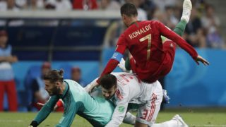 Portugal's forward Cristiano Ronaldo (R) falls over Spain's defender Gerard Pique (C) and Spain's goalkeeper David De Gea during the Russia 2018 World Cup Group B football match between Portugal and Spain at the Fisht Stadium in Sochi on June 15, 2018. / AFP PHOTO / Adrian DENNIS / RESTRICTED TO EDITORIAL USE - NO MOBILE PUSH ALERTS/DOWNLOADS