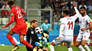 Dele Alli of England, left, challenges goalkeeper Mouez Hassen of Tunisia in their Group G match during the 2018 FIFA World Cup in Volgograd, Russia, 18 June 2018.  Harry Kane fired an injury time winner as he scored twice to earn England a 2-1 win over Tunisia in their World Cup opener. England got off to a quick start in Volgograd as Kane opened his account after just 11 minutes, tapping home after Tunisian goalkeeper Mouez Hassen pulled off an acrobatic save to deny John Stones. The Three Lions kicked into gear and came close several times, with Raheem Sterling missing a sitter and Hassen pulling off another stunning stop to prevent Jesse Lingard putting England two ahead. But Tunisia were gifted a way back into the game on 35 minutes, as Kyle Walker caught Ben Youssef with an arm in the England box and gave away a penalty. The Three Lions were dominant in possession but at times laboured under the pressure of the occasion, failing to break down Tunisia as the African side defended in numbers.