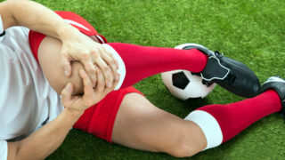 Close-up Of Male Soccer Player Suffering From Knee Injury On Field