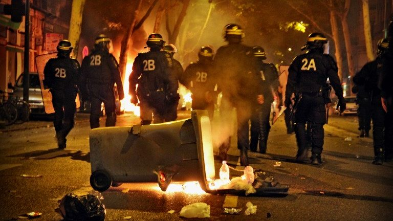 Police officers face rioters after French soccer fans celebrated World Cup victory over Croatia in Lyon, western France on July 15, 2018 after the Russia 2018 World Cup final football match between France and Croatia.