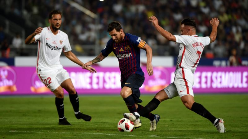 Barcelona's Argentinian forward Lionel Messi (C) vies with Sevilla's Spanish midfielder Roque Mesa under the look of Sevilla's Italian midfielder Franco Vazquez (L) during the Spanish Super Cup final between Sevilla and FC Barcelona at Ibn Batouta stadium in the Moroccan city of Tangiers on August 12, 2018. / AFP PHOTO / FADEL SENNA