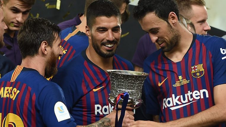 Barcelona's Argentinian forward Lionel Messi (2nd-L) presents the cup to Barcelona's Spanish midfielder Sergio Busquets (2nd-R) next to Barcelona's Uruguayan forward Luis Suarez (C) as they celebrate at the end of the Spanish Super Cup final between Sevilla FC and FC Barcelona at Ibn Batouta Stadium in the Moroccan city of Tangiers on August 12, 2018. Barcelona defeated Sevilla 2-1 to win the Spanish Super Cup. / AFP PHOTO / FADEL SENNA