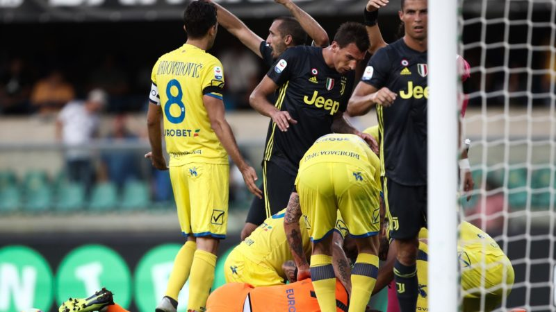 Players tend to Chievo's injured goalkeeper, Stefano Sorrentino (Bottom) after he collided with Juventus' Portuguese forward, Cristiano Ronaldo (R) during the Italian Serie A football match AC Chievo vs Juventus at the Marcantonio-Bentegodi stadium in Verona on August 18, 2018. / AFP PHOTO / Isabella BONOTTO