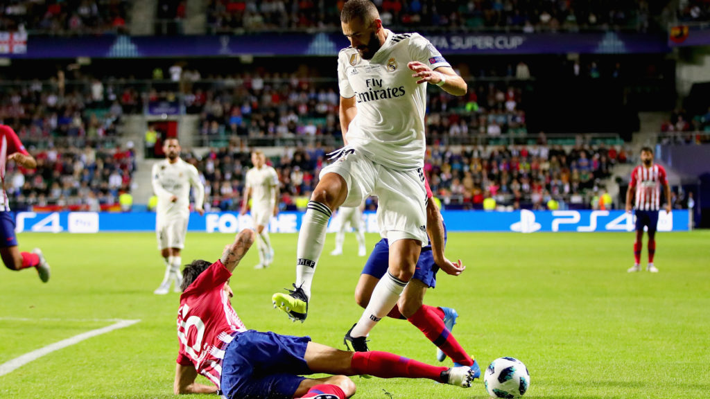 TALLINN, ESTONIA - AUGUST 15: Karim Benzema of Real Madrid jumps over a tackle from Stefan Savic of Atletico Madrid during the UEFA Super Cup between Real Madrid and Atletico Madrid at Lillekula Stadium on August 15, 2018 in Tallinn, Estonia.  (Photo by Chris Brunskill/Fantasista/Getty Images)