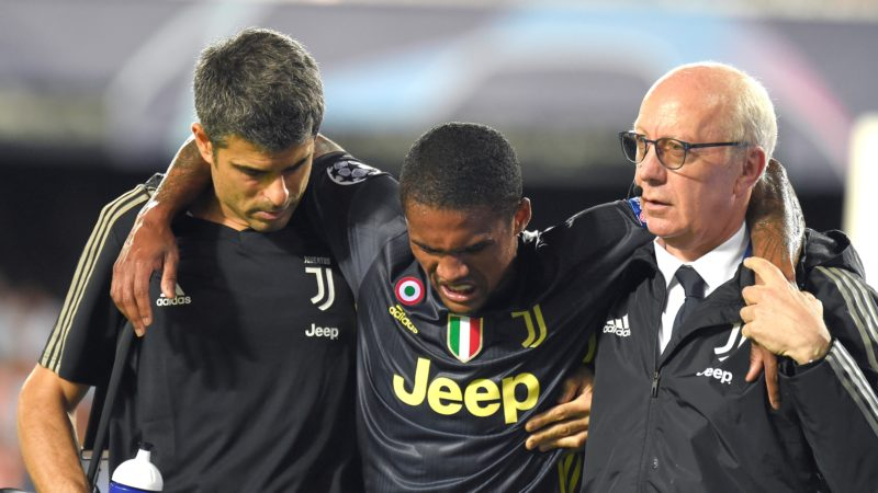 Juventus's Brazilian forward Douglas Costa (C) gestures in pain during the UEFA Champions League group H football match between Valencia CF and Juventus FC at the Mestalla stadium in Valencia on September 19, 2018. / AFP PHOTO / JOSE JORDAN