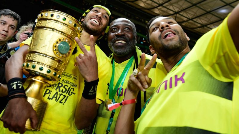 Dortmund's Gabonese forward Pierre-Emerick Aubameyang (L) and his father Pierre Francois Aubameyang (C) and brother Willy Aubameyang celebrate with the trophy after victory during the German Cup (DFB Pokal) final football match Eintracht Frankfurt v BVB Borussia Dortmund at the Olympic stadium in Berlin on May 27, 2017. / AFP PHOTO / Tobias SCHWARZ / RESTRICTIONS: ACCORDING TO DFB RULES IMAGE SEQUENCES TO SIMULATE VIDEO IS NOT ALLOWED DURING MATCH TIME. MOBILE (MMS) USE IS NOT ALLOWED DURING AND FOR FURTHER TWO HOURS AFTER THE MATCH. == RESTRICTED TO EDITORIAL USE == FOR MORE INFORMATION CONTACT DFB DIRECTLY AT +49 69 67880   /