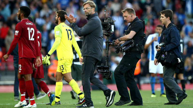 LIVERPOOL, ENGLAND - AUGUST 25: A camera operator films Jurgen Klopp applauding the fans during the Premier League match between Liverpool FC and Brighton & Hove Albion at Anfield on August 25, 2018 in Liverpool, United Kingdom. (Photo by Jan Kruger/Getty Images)
