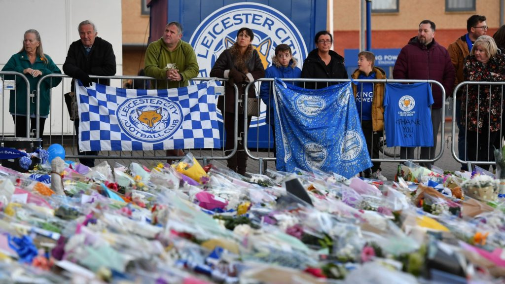 Supporters pause at the pile of floral tributes outside Leicester City Football Club's King Power Stadium in Leicester, eastern England, on October 28, 2018 after a helicopter belonging to the club's Thai chairman Vichai Srivaddhanaprabha crashed outside the stadium the night before. - Leicester City's charismatic Thai chairman was the subject of growing concerns on October 28 after a helicopter belonging to the billionaire crashed and burst into flames in the stadium car park shortly after taking off from the club's pitch following the match against West Ham United on October 27. There was no confirmation whether London-based Vichai Srivaddhanaprabha, who frequently flies to and from Leicester's home games by helicopter, was on board the aircraft which appeared to develop mechanical problems. (Photo by Ben STANSALL / AFP)