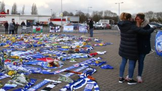 """Romina Sala (R), sister of Cardiff City's missing Argentinian footballer Emiliano Sala, whose flight disappeared from radar over the English Channel north of Guernsey, and a friend (R) reacts as she visits the tributes to Emiliano Sala layed outside Cardiff City Stadium in Cardiff, south Wales on January 25, 2019. - Police on January 24, 2019 ended their search for Premier League player Emiliano Sala, saying the chances of finding the Argentinian alive three days after his small plane went missing over the Channel were """"extremely remote"""". Their decision was met with anguished disbelief by the forward's sister Romina, who, speaking through tears, begged the search teams not to give up. The light aircraft transporting the 28-year-old striker, who signed for Cardiff City at the weekend, disappeared from radar around 20 kilometres (12 miles) north of Guernsey on the night of January 21. (Photo by GEOFF CADDICK / AFP)"""