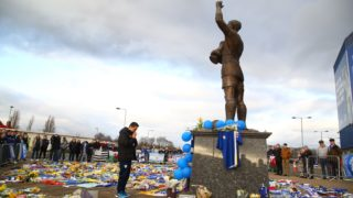 """Cardiff City FC Executive Director and CEO Ken Choo pauses at the scarves and jerseys, flowers, messages and other tributes to the football club's new signing Emiliano Sala, whose flight disappeared from radar over the English Channel north of Guernsey, outside the Cardiff City Stadium in Cardiff, south Wales on January 25, 2019. - Police on January 24, 2019 ended their search for Premier League player Emiliano Sala, saying the chances of finding the Argentinian alive three days after his small plane went missing over the Channel were """"extremely remote"""". Their decision was met with anguished disbelief by the forward's sister Romina, who, speaking through tears, begged the search teams not to give up. The light aircraft transporting the 28-year-old striker, who signed for Cardiff City at the weekend, disappeared from radar around 20 kilometres (12 miles) north of Guernsey on the night of January 21. (Photo by GEOFF CADDICK / AFP)"""