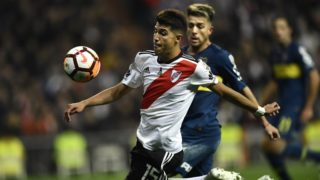River Plate's Exequiel Palacios takes the ball past Boca Juniors' Julio Buffarini during the second leg match of their all-Argentine Copa Libertadores final, at the Santiago Bernabeu stadium in Madrid, on December 9, 2018. (Photo by OSCAR DEL POZO / AFP)