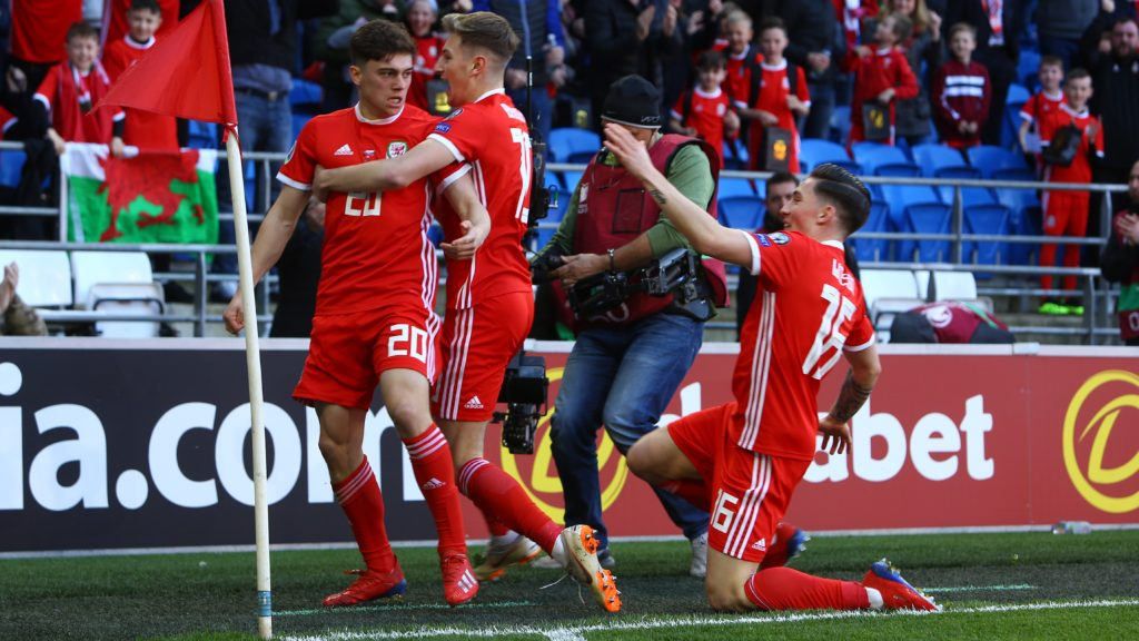 Wales' midfielder Daniel James (L) celebrates with Wales' midfielder David Brooks (C) and Wales' midfielder Harry Wilson (R) after scoring their early opening goal during the UEFA Euro 2020 Group E qualification football match between Wales and Slovakia at Cardiff City Stadium in Cardiff on March 24, 2019. (Photo by Geoff CADDICK / AFP)