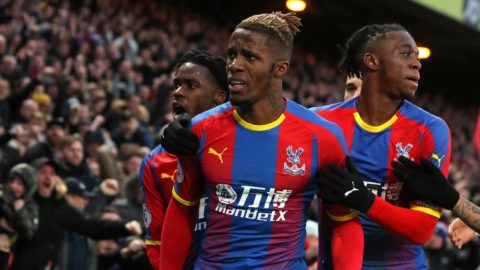 Crystal Palace's Ivorian striker Wilfried Zaha (C) celebrates with teammates after scoring their first goal during the English Premier League football match between Crystal Palace and West Ham United at Selhurst Park in south London on February 9, 2019. (Photo by Daniel LEAL-OLIVAS / AFP) / RESTRICTED TO EDITORIAL USE. No use with unauthorized audio, video, data, fixture lists, club/league logos or 'live' services. Online in-match use limited to 120 images. An additional 40 images may be used in extra time. No video emulation. Social media in-match use limited to 120 images. An additional 40 images may be used in extra time. No use in betting publications, games or single club/league/player publications. /