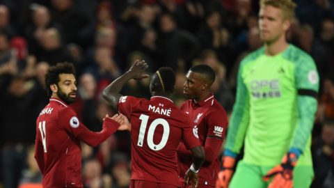 Liverpool's Egyptian midfielder Mohamed Salah (L) celebrates with teammates after he scores the team's third goal during the English Premier League football match between Liverpool and Huddersfield at Anfield in Liverpool, north west England on April 26, 2019. (Photo by Oli SCARFF / AFP) / RESTRICTED TO EDITORIAL USE. No use with unauthorized audio, video, data, fixture lists, club/league logos or 'live' services. Online in-match use limited to 120 images. An additional 40 images may be used in extra time. No video emulation. Social media in-match use limited to 120 images. An additional 40 images may be used in extra time. No use in betting publications, games or single club/league/player publications. /