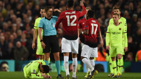 Barcelona's Argentinian forward Lionel Messi (C) is injured during the UEFA Champions league first leg quarter-final football match between Manchester United and Barcelona at Old Trafford in Manchester, north west England, on April 10, 2019. (Photo by Oli SCARFF / AFP)