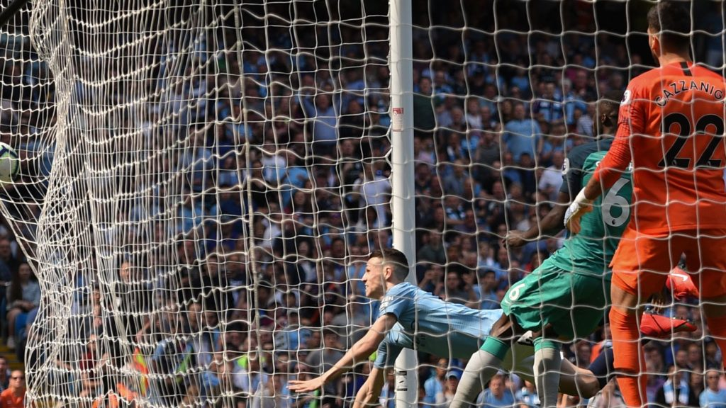 Manchester City's English midfielder Phil Foden scores the opening goal (L) during the English Premier League football match between Manchester City and Tottenham Hotspur at the Etihad Stadium in Manchester, north west England, on April 20, 2019. (Photo by Oli SCARFF / AFP) / RESTRICTED TO EDITORIAL USE. No use with unauthorized audio, video, data, fixture lists, club/league logos or 'live' services. Online in-match use limited to 120 images. An additional 40 images may be used in extra time. No video emulation. Social media in-match use limited to 120 images. An additional 40 images may be used in extra time. No use in betting publications, games or single club/league/player publications. /