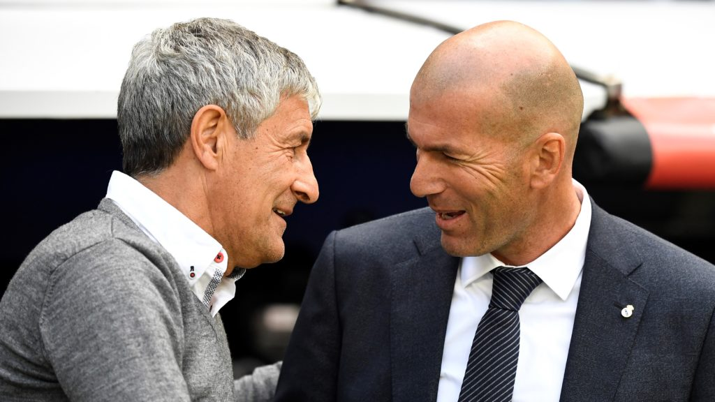 Real Madrid's French coach Zinedine Zidane (R) speaks to Real Betis' Spanish coach Quique Setien before the Spanish League football match between Real Madrid and Real Betis at the Santiago Bernabeu stadium in Madrid on May 19, 2019. (Photo by PIERRE-PHILIPPE MARCOU / AFP)