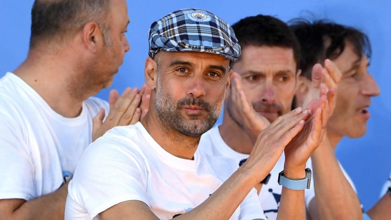 Manchester City's Spanish manager Pep Guardiola (C) and memners of his training team take part in a stage presentation following an open-top bus parade through Manchester, northern England on May 20, 2019, to celebrate winning the 2019 Premier League title, the FA Cup and English League Cup. - Pep Guardiola saluted Manchester City's history makers after they clinched the domestic treble with a swaggering 6-0 rout of Watford in the FA Cup final on Saturday. Just a week after winning a second successive Premier League crown, City's record-equalling FA Cup final victory made them the first English club to win the English title, FA Cup and League Cup in the same season. (Photo by Paul ELLIS / AFP)