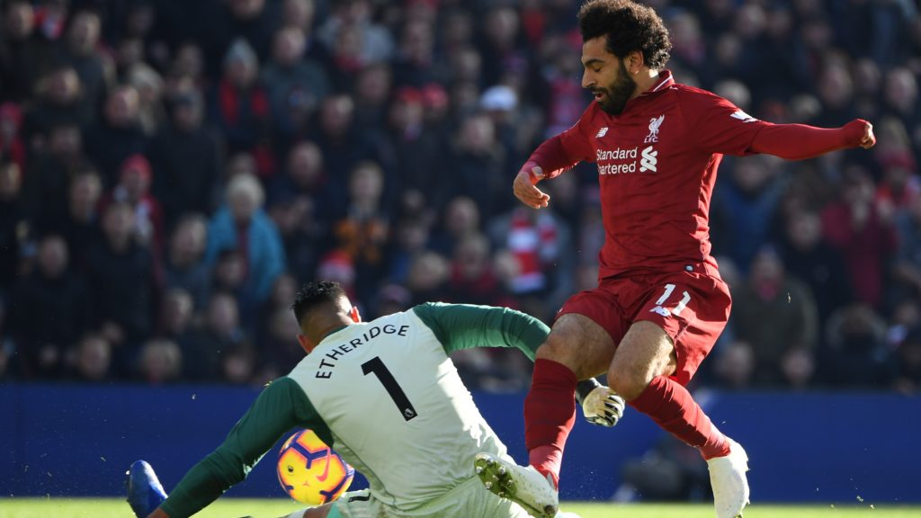 Cardiff City's English-born Filipino goalkeeper Neil Etheridge (L) saves from Liverpool's Egyptian midfielder Mohamed Salah (R) during the English Premier League football match between Liverpool and Cardiff City at Anfield in Liverpool, north west England on October 27, 2018. (Photo by Paul ELLIS / AFP) / RESTRICTED TO EDITORIAL USE. No use with unauthorized audio, video, data, fixture lists, club/league logos or 'live' services. Online in-match use limited to 120 images. An additional 40 images may be used in extra time. No video emulation. Social media in-match use limited to 120 images. An additional 40 images may be used in extra time. No use in betting publications, games or single club/league/player publications. /