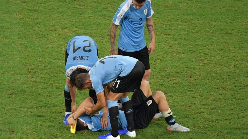 Uruguay's Luis Suarez (on the ground) -whose penalty was stopped by Peru's goalkeeper Pedro Gallese- is comforted by teammates Edinson Cavani (L), Cristhian Stuani (C) and Jose Maria Gimenez (top) after losing in the penalty shoot-out 5-4 after tying 0-0 during their Copa America football tournament quarter-final match at the Fonte Nova Arena in Salvador, Brazil, on June 29, 2019. (Photo by Luis ACOSTA / AFP)