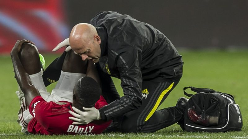 Manchester United's injured  Eric Bailly receives medical treatment during their pre-season friendly football match against Leeds United at Optus Stadium in Perth on July 17, 2019. (Photo by TONY ASHBY / AFP) / -- IMAGE RESTRICTED TO EDITORIAL USE - STRICTLY NO COMMERCIAL USE --