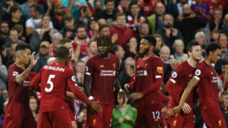 Liverpool's Belgium striker Divock Origi  (C) celebrates with teammates after he scores the team's fourth goal during the English Premier League football match between Liverpool and Norwich City at Anfield in Liverpool, north west England on August 9, 2019. (Photo by Oli SCARFF / AFP) / RESTRICTED TO EDITORIAL USE. No use with unauthorized audio, video, data, fixture lists, club/league logos or 'live' services. Online in-match use limited to 120 images. An additional 40 images may be used in extra time. No video emulation. Social media in-match use limited to 120 images. An additional 40 images may be used in extra time. No use in betting publications, games or single club/league/player publications. /