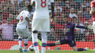 Crystal Palace's French-born Ghanaian striker Jordan Ayew (L) shoots past Manchester United's Spanish goalkeeper David de Gea (R) to score the opening goal during the English Premier League football match between Manchester United and Crystal Palace at Old Trafford in Manchester, north west England, on August 24, 2019. (Photo by Lindsey Parnaby / AFP) / RESTRICTED TO EDITORIAL USE. No use with unauthorized audio, video, data, fixture lists, club/league logos or 'live' services. Online in-match use limited to 120 images. An additional 40 images may be used in extra time. No video emulation. Social media in-match use limited to 120 images. An additional 40 images may be used in extra time. No use in betting publications, games or single club/league/player publications. /