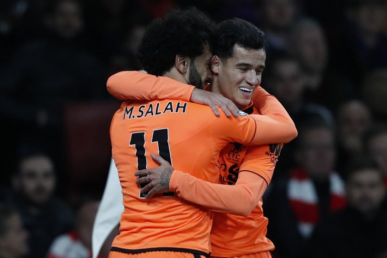 Liverpool's Brazilian midfielder Philippe Coutinho (R) celebrates with Liverpool's Egyptian midfielder Mohamed Salah after scoring the team's first goal during the English Premier League football match between Arsenal and Liverpool at the Emirates Stadium in London on December 22, 2017.  / AFP PHOTO / Adrian DENNIS / RESTRICTED TO EDITORIAL USE. No use with unauthorized audio, video, data, fixture lists, club/league logos or 'live' services. Online in-match use limited to 75 images, no video emulation. No use in betting, games or single club/league/player publications.  /