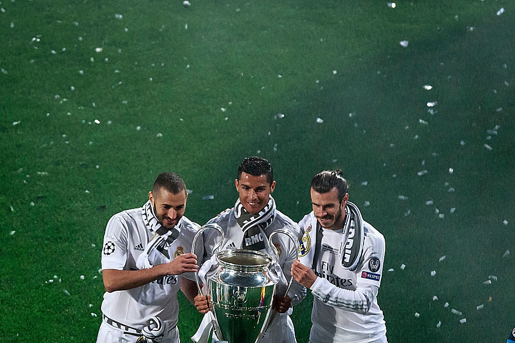 MADRID, SPAIN - MAY 29: Cristiano Ronaldo (2ndL) of Real Madrid CF holds the trophy as he poses for a picture with his teammates Karim Benzema (L) and Gareth Bale (R) during the celebration with their fans at Santiago Bernabeu Stadium the day after winning the UEFA Champions League Final match against Club Atletico de Madrid on May 29, 2016 in Madrid, Spain. Real Madrid CF is the only European football team with 11 European Cups (Photo by Gonzalo Arroyo Moreno/Getty Images)