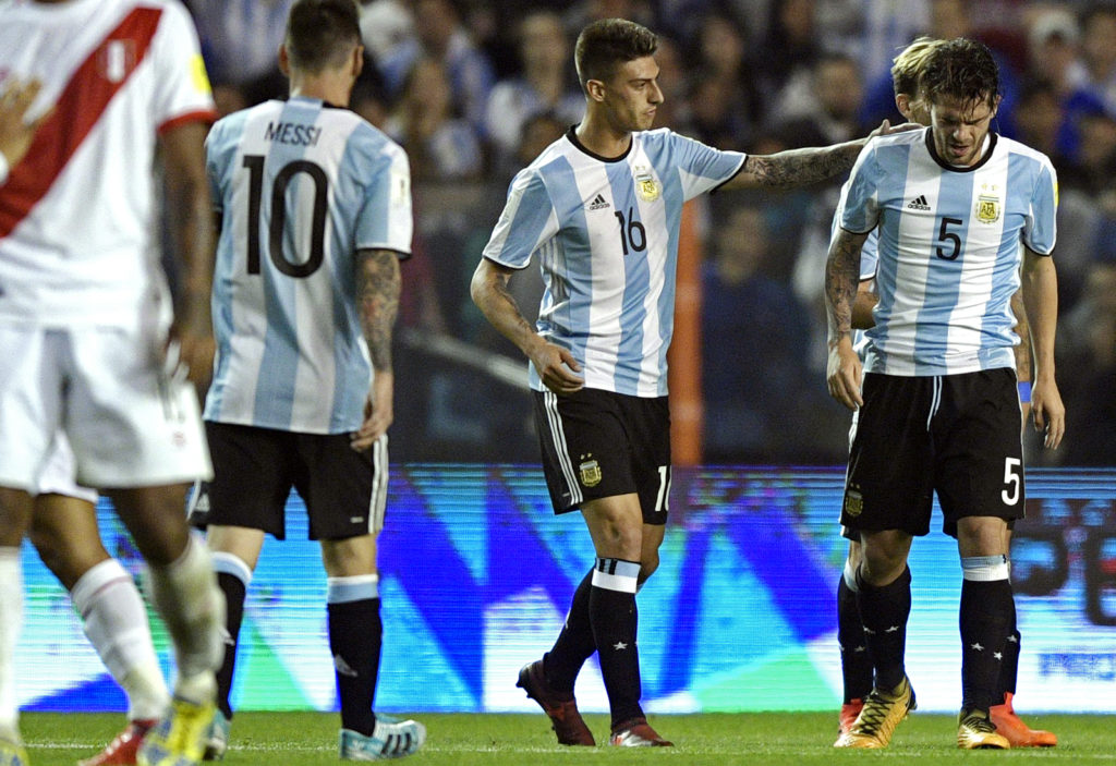 Argentina's Emiliano Rigoni (2-R) comforts teammate Fernando Gago as he leaves the field in pain during the 2018 World Cup football qualifier match against Peru in Buenos Aires on October 5, 2017. / AFP PHOTO / Juan MABROMATA