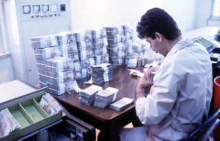 An unidentified banker sorts banknotes at a table in the Central Bank of Iran, Tehran, Iran, March 1, 1992. (Photo by Kaveh Kazemi/Getty Images)