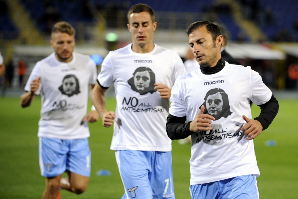 """BOLOGNA, BOLOGNA - OCTOBER 25:  Stefan Radu of Lazio wears a shirt depicting Anne Frank saying """"no to anti-Semitism"""", in response to anti-semitic graffiti left by their fans at a previous match, during the Serie A match between Bologna FC and SS Lazio at Stadio Renato Dall'Ara on October 25, 2017 in Bologna, Italy.  (Photo by Marco Rosi/Getty Images)"""