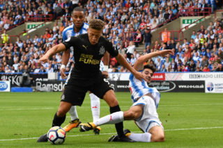 Newcastle United's English forward Dwight Gayle (L) is tackled in the penalty area during the English Premier League football match between Huddersfield Town and Newcastle United at the John Smith's stadium in Huddersfield, northern England on August 20, 2017. / AFP PHOTO / Anthony Devlin / RESTRICTED TO EDITORIAL USE. No use with unauthorized audio, video, data, fixture lists, club/league logos or 'live' services. Online in-match use limited to 75 images, no video emulation. No use in betting, games or single club/league/player publications.  /