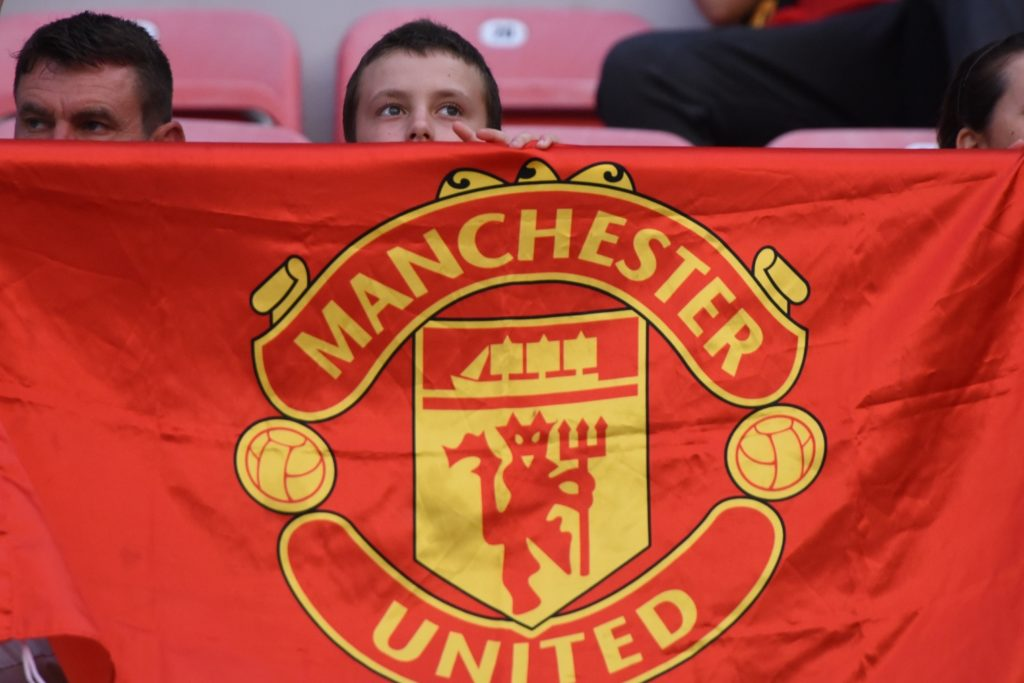 A boy displays a Manchester United flag prior to the UEFA Super Cup football match between Real Madrid and Manchester United on August 8, 2017, at the Philip II Arena in Skopje. / AFP PHOTO / ARMEND NIMANI