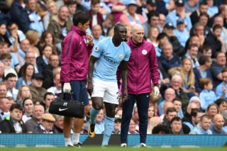 Manchester City's French defender Benjamin Mendy (C) is helped by medics during the English Premier League football match between Manchester City and Crystal Palace at the Etihad Stadium in Manchester, north west England, on September 23, 2017. / AFP PHOTO / Oli SCARFF / RESTRICTED TO EDITORIAL USE. No use with unauthorized audio, video, data, fixture lists, club/league logos or 'live' services. Online in-match use limited to 75 images, no video emulation. No use in betting, games or single club/league/player publications.  /