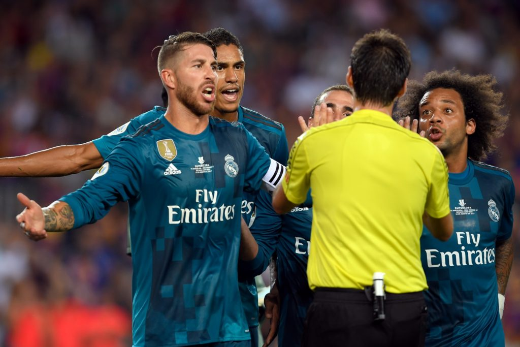 Real Madrid's defender Sergio Ramos (L), Real Madrid's French defender Raphael Varane (2L) and Real Madrid's Brazilian defender Marcelo (R) protest to the referee during the Spanish Supercup first leg football match FC Barcelona vs Real Madrid at the Camp Nou stadium in Barcelona on August 13, 2017. / AFP PHOTO / LLUIS GENE